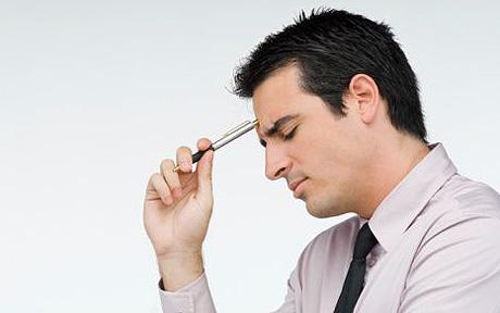 Close-up of a businessman holding a pen and thinking